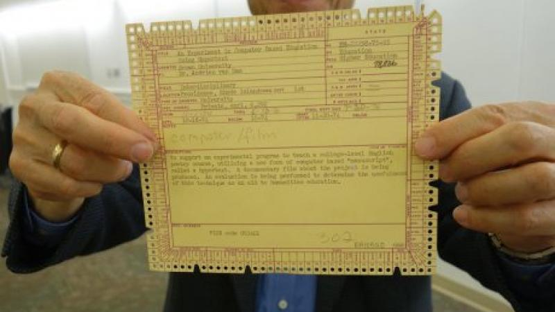 A man holding a yellow McBee punch card up close to the camera.