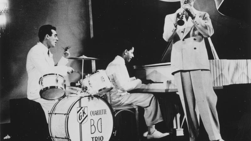 Black and white photo of a jazz trio, with one man on the drums, another on the piano, and the last one on the clarinet.