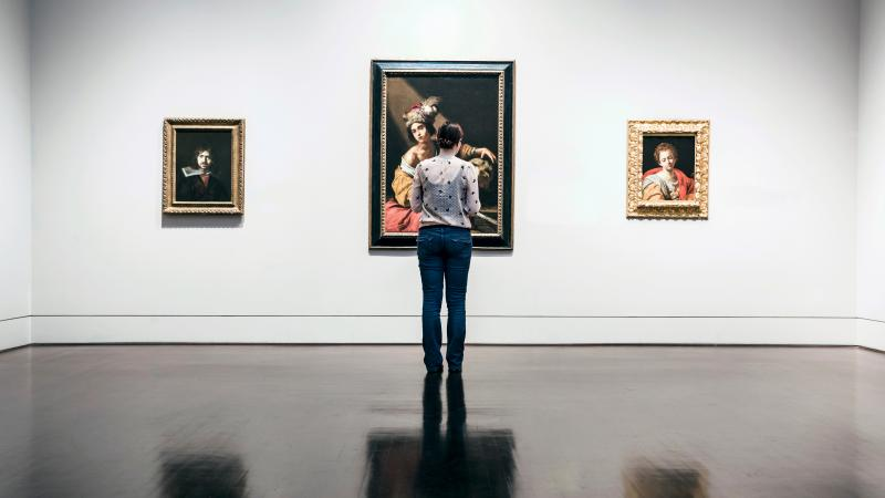 Photograph of woman standing in museum, three paintings on the wall