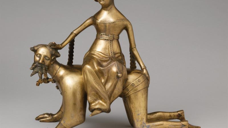 Gold figure of Phyllis riding atop an Aristotle on all fours, as if he were a dog.