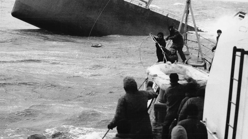 Black and white photo of men pulling in a life raft from a sinking ship.