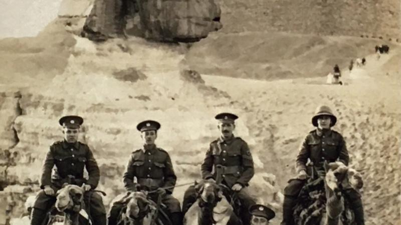 Sepia-colored photo of mounted soldiers posing before the pyramids of Egypt.