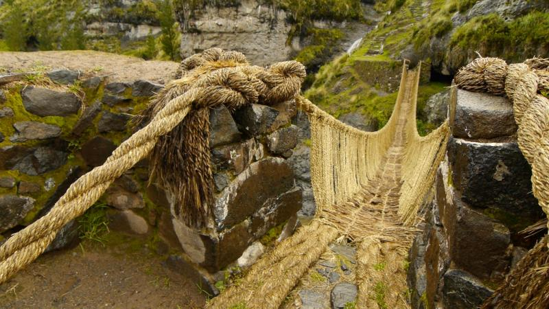 bridge made from thick, braided yellow rope, which dips down and over a chasm, with a river flowing below