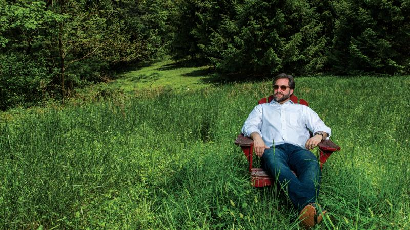 Photograph of man sitting in adirondack chair in tall grass