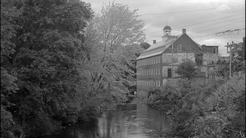 black and white photograph of a stream, building off of the bank