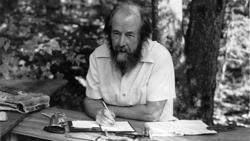 black and white photo of a bearded man writing at a table