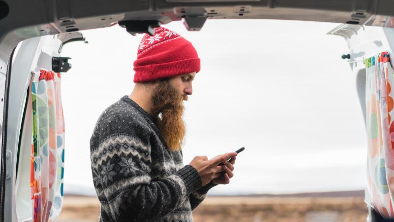 Hipster man looks at his phone in the outdoors.
