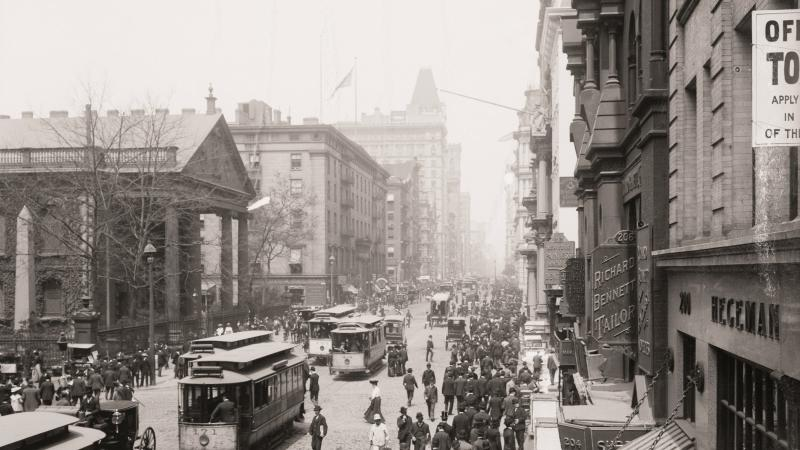 Black and white photograph of a busy city street, people on sidewalks