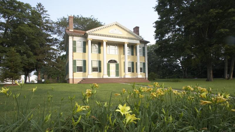 Photo of a restored mansion in a field of grass