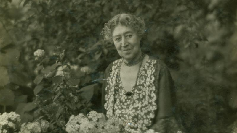 Photograph of a woman sitting in a garden
