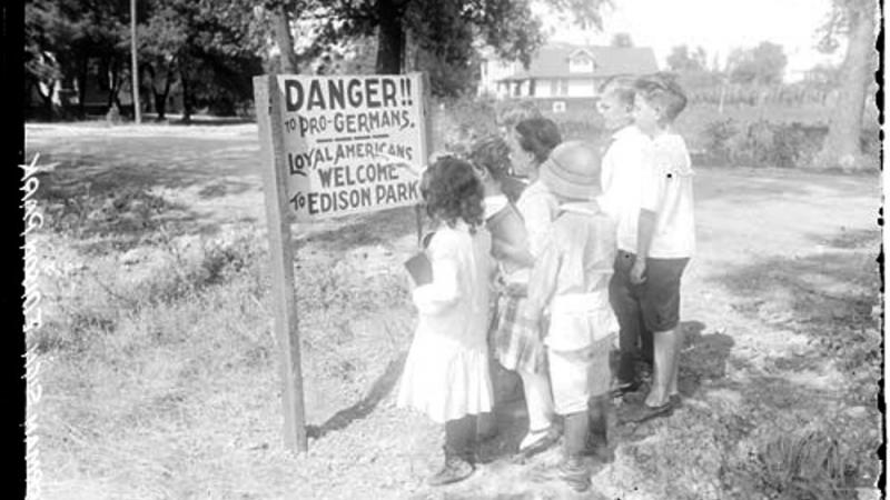 Children Standing in front of an anti-German sign posted in Edison Park.