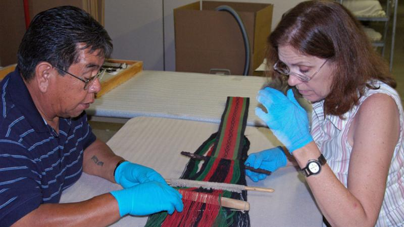 Conservator and Hopi weaver working on a piece