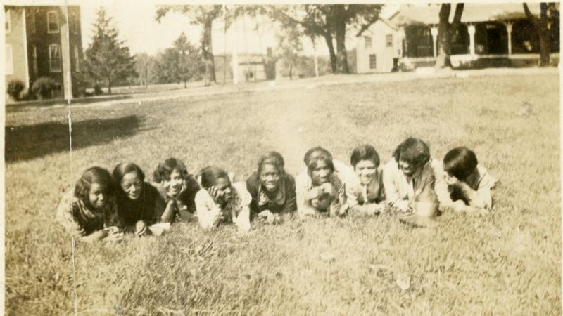 Early campus photograph of girls in the grass