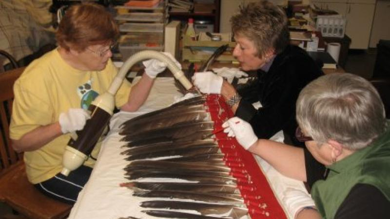 photograph of three women cleaning a feathered headdress
