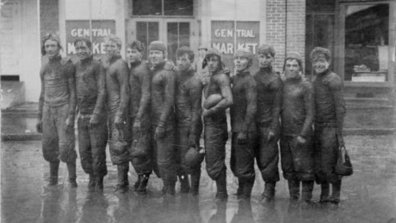 black and white photo of football team standing in the rain
