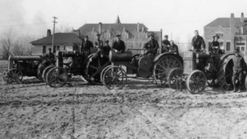 black and white photo of men standing on tractors in field
