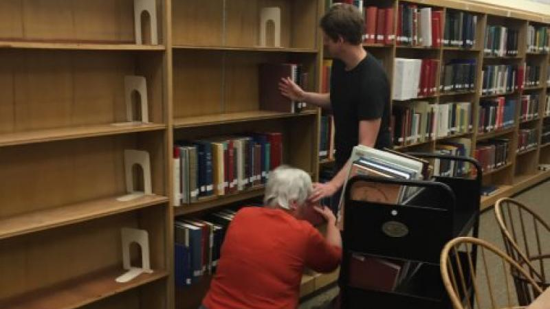 two people removing books from bookshelf