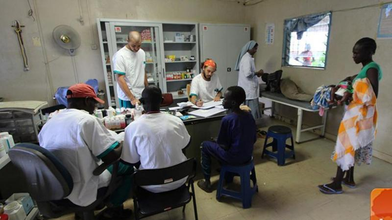 Photograph of clinic with various doctors working around a table