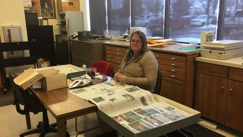 Michele Wheeler working on identifying Vernal Express photos using newspapers.