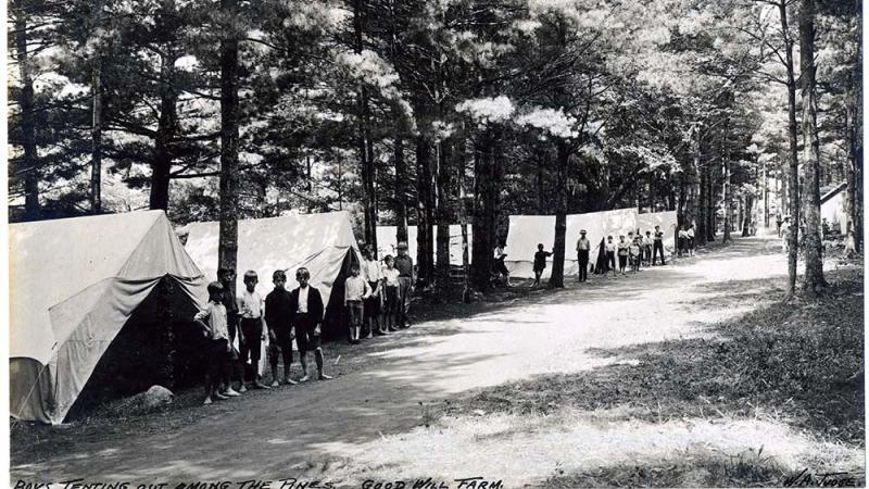 black and white photo of a row of tents, boys standing in front of them