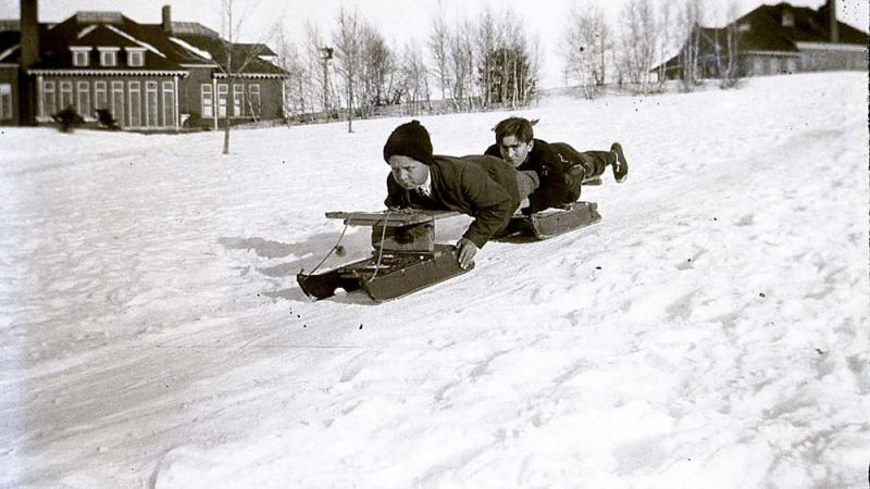black and white photo of two boys sledding down a snowy hill