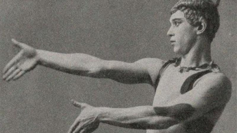 Black and white portrait of a man standing in a ballerina pose with his arms extended.