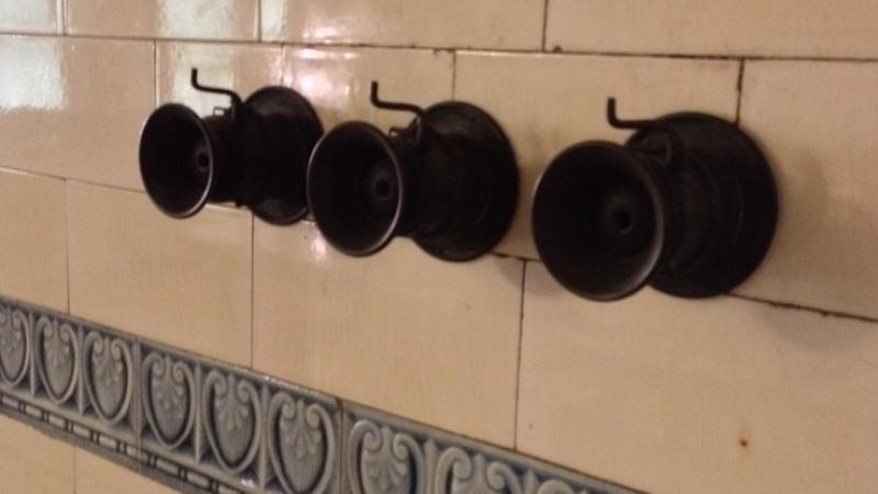 Speaking tubes fastened to a tile wall