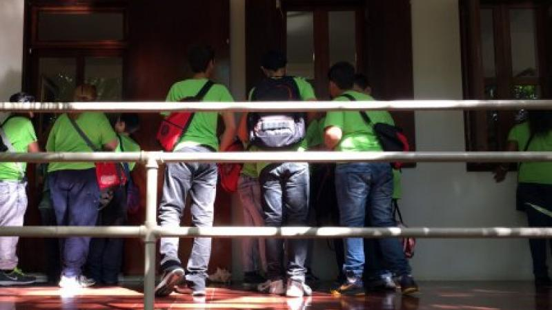 photograph of kids in green shirts entering a house
