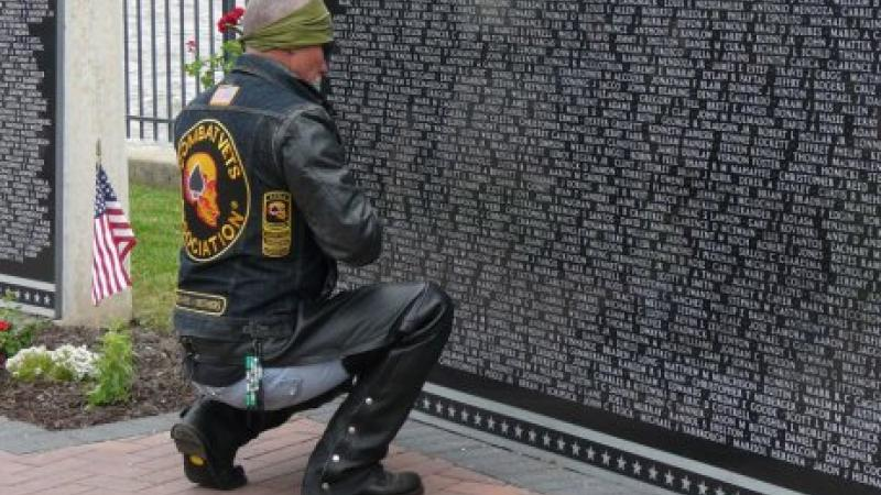 A man in jeans and a motorcycle jacket kneels before the Vietnam War Memorial.