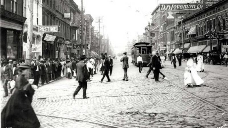 Black and white photo of a busy city street with people crossing and a trolley in the distance.