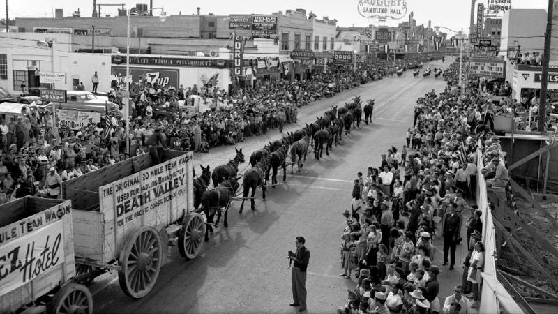 black and white photograph looking down a crowded street, parade occurring