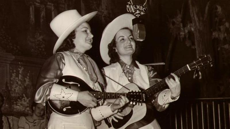 Kitty & Kay performing with guitar and mandolin.