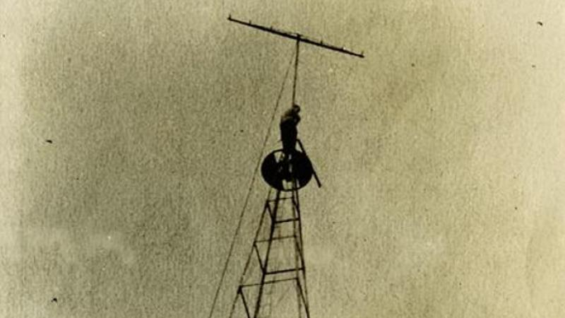 Radio tower with a man near top by antenna at Graceland College, Lamoni, Iowa.