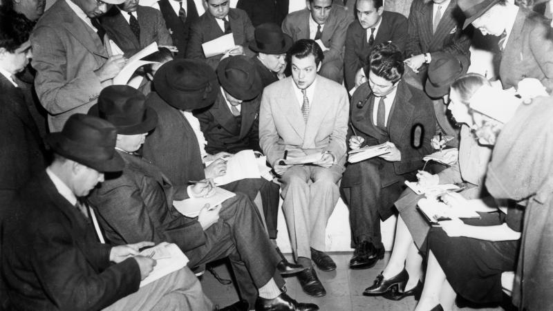 Orson Welles in the middle of journalists