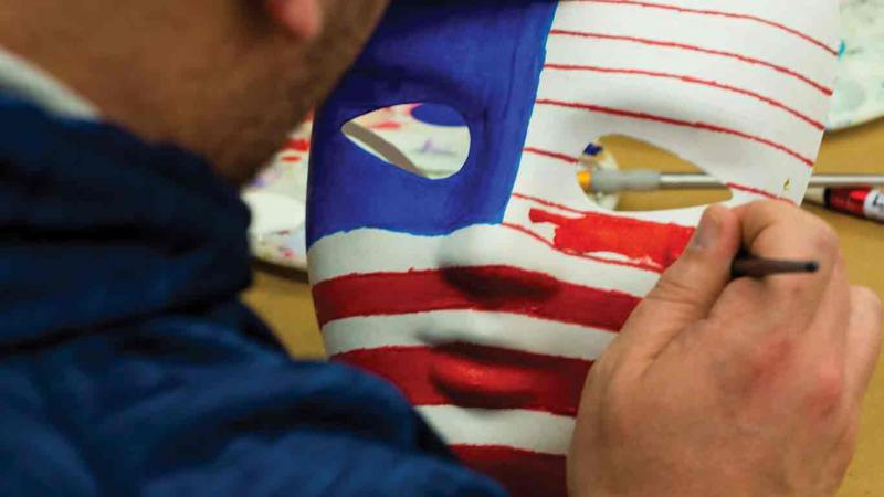 Veteran Darren LeMorta paints an  American flag on a mask