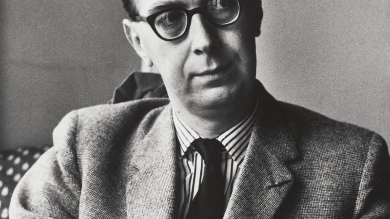 Philip Larkin, seated, looking thoughtful
