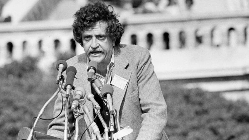 Kurt Vonnegut, speaking publicly, from behind behind a bouquet of microphones