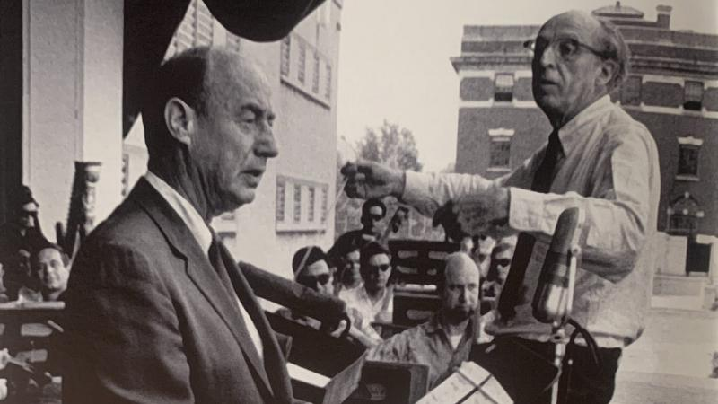 Black and white photo of Copland conducting Lincoln Portrait with Adlai Stevenson at Lewisohn Stadium.